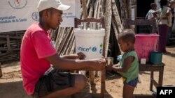 Un membre de l'ONG Action Contre la Faim donne de l'eau potable à un nourrisson lors d'une séance de dépistage de la malnutrition dans la commune d'Ifotaka, dans le sud de Madagascar, le 14 décembre 2018.