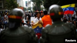 An opposition supporter holds a national flag as she shouts at the riot police during a protest against President Nicolas Maduro's government in Caracas, Feb. 17, 2014.