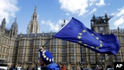 An anti-Brexit campaigner shows her support for Europe waving a European Union flag outside Parliament in London, March 25, 2019.