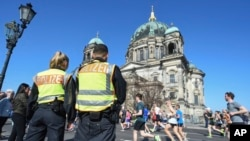 Maafisa wa polisi wakilinda doria katika mbio za nusu -marathon mbele ya Kanisa la Berlin, Berlin, Ujerumani, April 8, 2018.