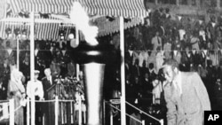 Prime Minister Robert Mugabe of the newly independent state of Zimbabwe, lights the Independence Flame, April 18, 1980, which is to burn eternally as a monument to black majority rule won through seven years of guerrilla warfare and political effort.