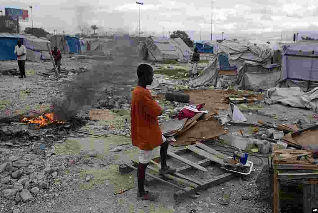 A youth stands among debris from tents disassembled by authorities who closed the camp occupied by people displaced by the 2010 earthquake near the airport in Port-au-Prince, Haiti, January. 4, 2012. (AP)