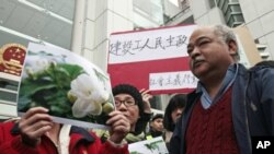 "Protesters hold up pictures of jasmine flowers during a ""Jasmine Revolution"" protest outside the Chinese liaison office in Hong Kong February 20, 2011. Government radio reported that mainland authorities have detained a number of activists as they react t"