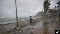 A man battles strong winds and rain from Typhoon Hagupit in Legazpi, Albay province, eastern Philippines, Dec. 7, 2014.