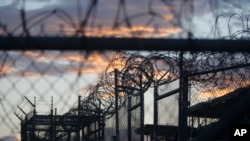 FILE - Dawn breaks at the now closed Camp X-Ray, used as the first detention facility for suspected militants captured after the Sept. 11 attacks, at the Guantanamo Bay Naval Base in Cuba, dawn arrives at the now closed Camp X-Ray, which was used as the f