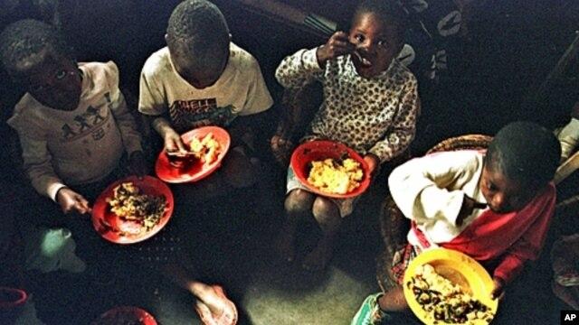 A group of young Rwandans eat at the orphanage run by American Rosamund Carr near Gisenyi, Rwanda, (File July 20, 1997).