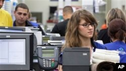 Cashier Jillian Capko, right, checks merchandise at a Sam's Club store, Rogers, Ark., June 2011 file photo.