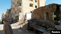 A man looks at damage at a site hit by what activists said was an airstrike by forces loyal to Syria's President Bashar al-Assad in Raqqa, an Islamic State power base in Syria, Sept. 8, 2014.