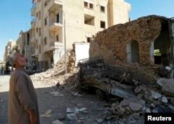 FILE - A man looks at damage at a site hit by what activists said was an airstrike by forces loyal to Syria's President Bashar al-Assad in Raqqa, an Islamic State power base in Syria, Sept. 8, 2014.