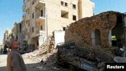 FILE - A man looks at damage at a site hit by what activists said was an airstrike by forces loyal to Syria's President Bashar al-Assad in Raqqa, Syria.