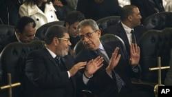 Musulmon Birodarlar partiyasidan prezidentlik uchun nomzod Muhammad Mursiy (chapda) Qohiradagi qibtiy nasorolar cherkovida. Agar prezidentlikka saylansa, Mursiy Misrda barchaning haq-huquqlari himoyalanishiga va'da bermoqda.