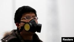 Một người đàn ông đeo mặt nạ đi trong khói mù dày đặc tại Bắc Kinh.