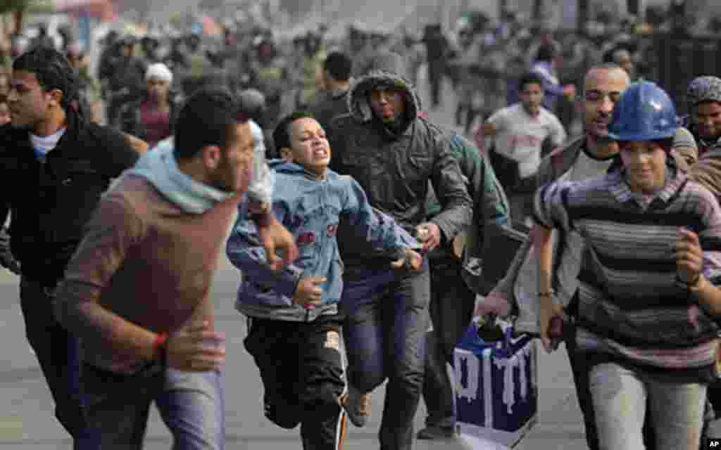 Egyptian protesters run as they are chased by army soldiers over the Asr el-Nile bridge leading out of Tahrir Square, in Cairo, Egypt, Saturday, Dec. 17, 2011. Hundreds of Egyptian soldiers swept into Cairo's Tahrir Square on Saturday, chasing protesters