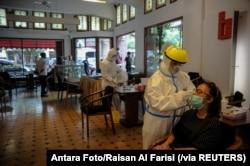 Para petugas medis mengambil sampel untuk tes cepat antigen dari para pengunjung di tengah pandemi virus coronca (COVID-19) di Bandung, Jawa Barat, Rabu, 30 Desember 2020. (Foto: Antara Foto/ Raisan Al Farisi via Reuters)