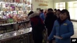 북한 평양 중구역 창전거리에 새로 문을 연 '황금벌' 상점을 찾은 손님들이 지난 2월 물건을 사고 있다. (자료사진)