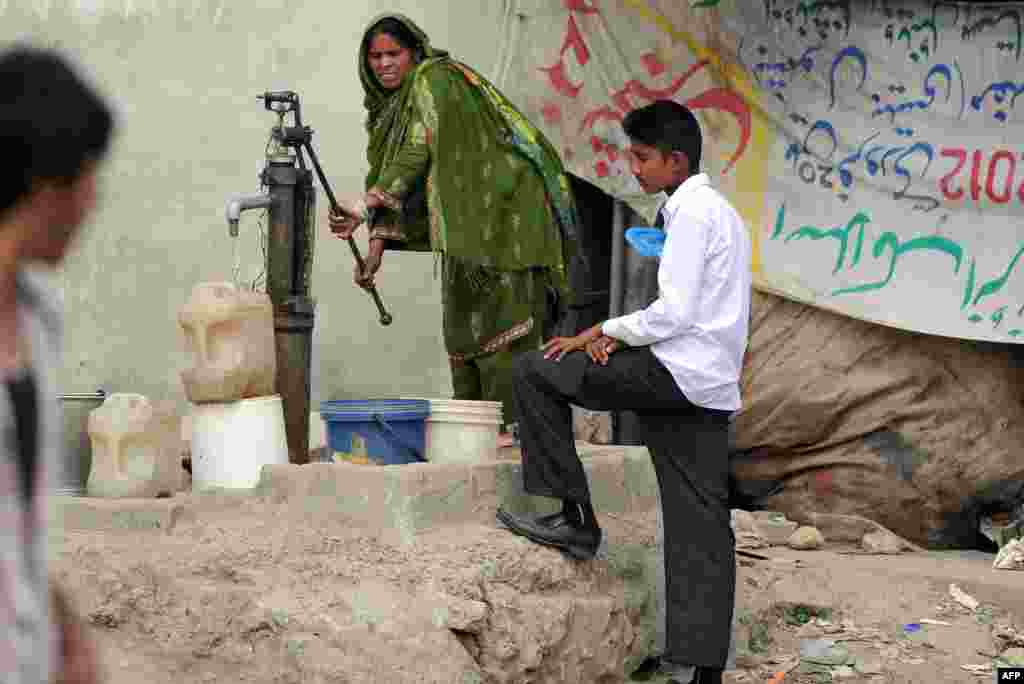 A Pakistani Christian woman fills jerry cans with water from a hand pump at a slum area of Islamabad.