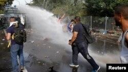 Polisi anti huru-hara Hungaria menembakkan meriam Roszke dan gas air mata terhadap para migran yang berusaha masuk ke kota Roszke, Rabu (16/9).