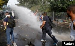 Migrants protest as Hungarian riot police fires tear gas and water cannon on the Serbian side of the border, near Roszke, Hungary Sept. 16, 2015.