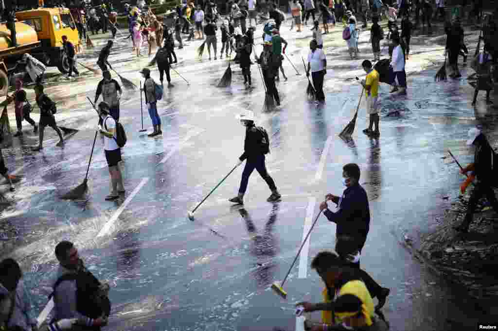 Anti-government protesters sweep the street around the Democracy Monument after weeks of protesting and days of clashes with police in Bangkok's city center, Dec. 4, 2013.