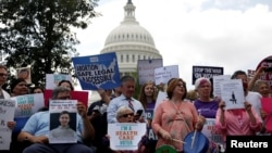 FILE - Activists participate in a rally to protect the Affordable Care Act outside the U.S. Capitol in Washington, Sept. 19, 2017.