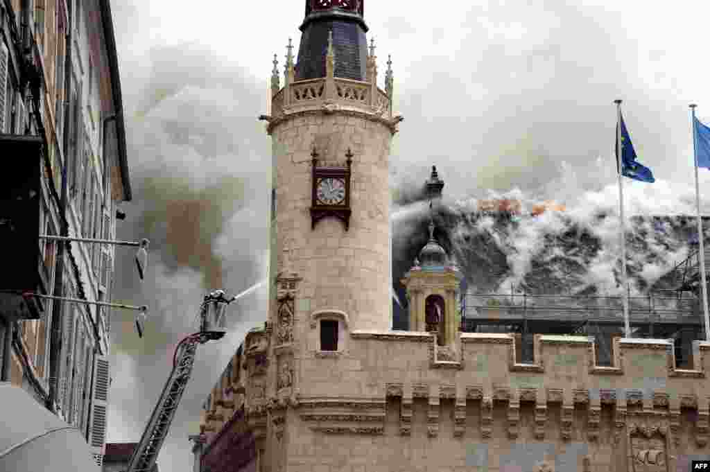 Firemen work to extinguish a fire that broke out in the city hall, in La Rochelle, western France. The fire swept through the roof destroying part of the historic 15th-century building.