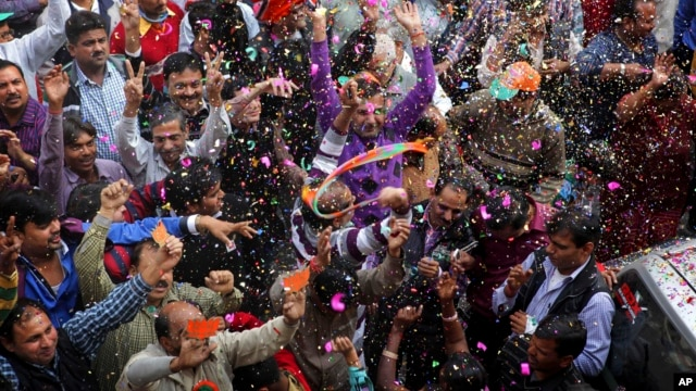 India's main opposition Bharatiya Janata Party, (BJP) supporters celebrate the party's victory in the Delhi state Assembly elections in New Delhi, Dec. 8, 2013.