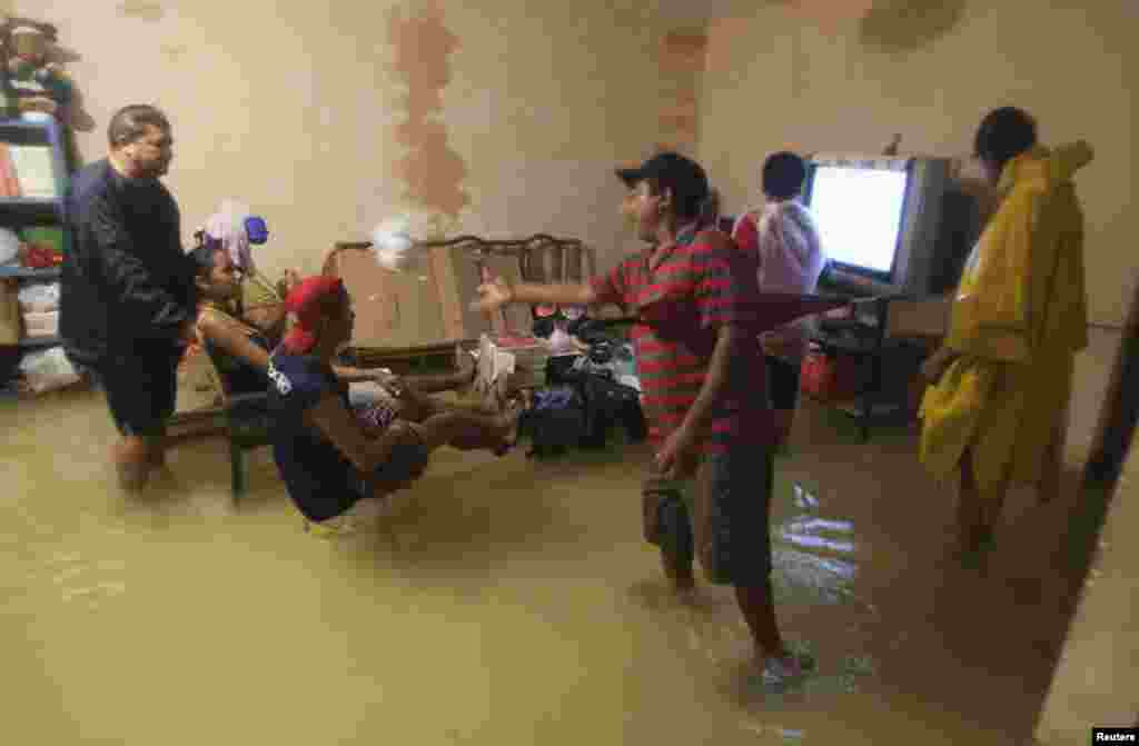 People try to watch television inside their flooded home in Mexico's resort city Cancun, June 4, 2013.