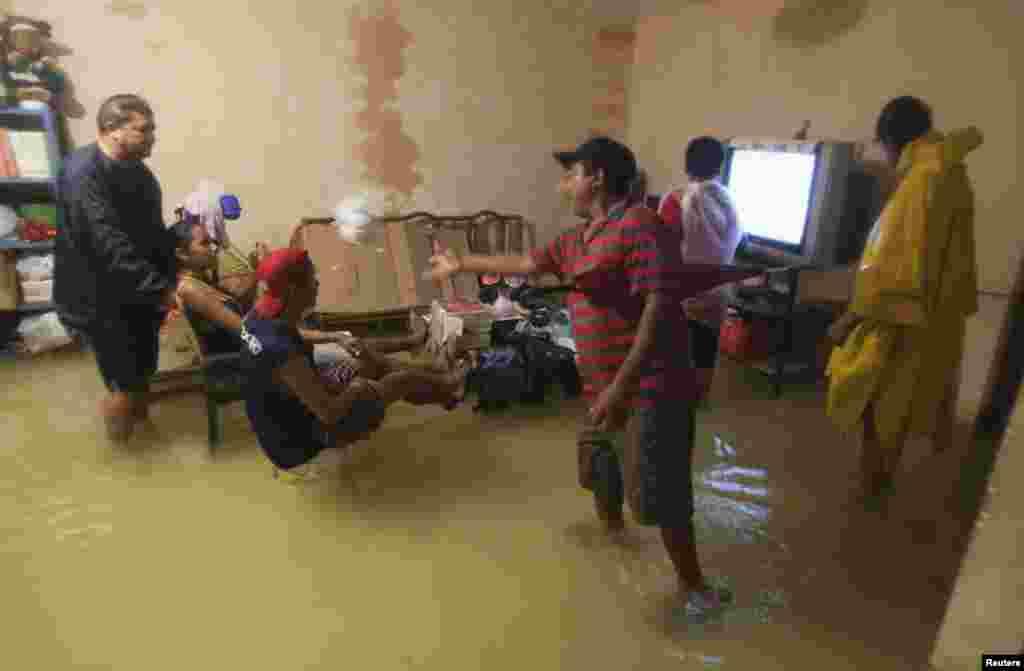 اهالی یک خانه در اتاقی سیلزده در کنکون مکزیک، مشغول تماشای تلویزیون