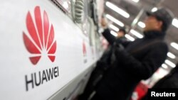 FILE - A man looks at a Huawei mobile phone as he shops at an electronic market in Shanghai.