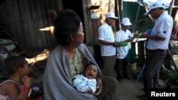 រូបឯកសារ៖ ស្ត្រីម្នាក់កំពុងបីចៅ ខណៈដែលមន្ត្រីសុខាភិបាលកំពុងបាញ់ថ្នាំសម្លាប់មូស និងដង្កូវទឹក នៅគេហដ្ឋានប្រជាពលរដ្ឋនៅរាជធានីភ្នំពេញ កាលពីថ្ងៃទី៤ ខែកុម្ភៈ ឆ្នាំ២០១៦។ (REUTERS/Samrang Pring)