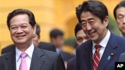 日本首相安倍晉三(右)1月16 日抵達越南﹐在河內和越南總理阮晉勇(左)談笑。