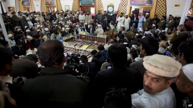 Maulana Abdul Aziz, center, in the background, the Red Mosque cleric and member of the Taliban negotiating team, addresses a news conference in Islamabad, Pakistan, Feb. 7, 2014.
