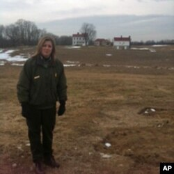 Joy Beasley, archeologist at Monocacy National Battlefield, stands next to the foundations of the slave village. The homes of the Vincendieres are in the background.