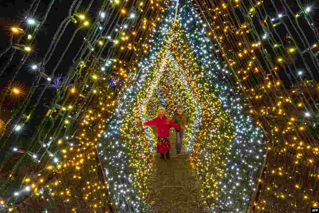 Children walk past 200,000 lights in a winter wonderland at Naumkeag, part of the land managed by the Trustees of Reservations, in Stockbridge, Massachusetts, USA, December 13, 2020.