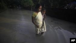 Phụ nữ Ấn Ðộ bồng con lội qua một con đường bị ngập nước ở làng Chandrapur, ngoại ô Gauhati, bang Assam, ngày 25/9/2012