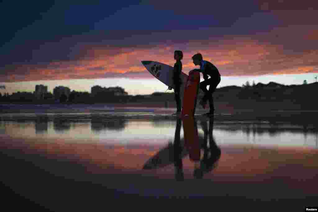 Những người lướt sóng trẻ tuổi đứng chờ bạn lướt sóng xong vào lúc chiều tà bãi biển Wanda tại Sydney, Australia.