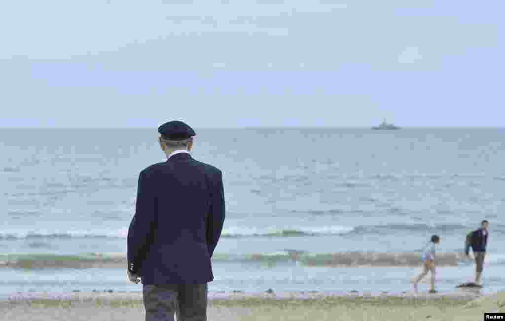 British D-Day veteran George French, 88, from Wiltshire, who served with King's Royal Rifles looks out to the water as he stands on Sword Beach at Hermanville-sur-Mer on the Normandy coast June 5, 2014.