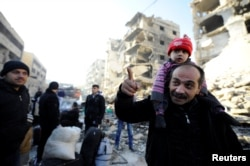 People, who evacuated the eastern districts of Aleppo, stand with their belongings in a government held area of Aleppo, Syria Dec. 9, 2016.