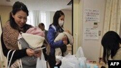 Các bà mẹ nhận được nước đóng chai tại một trung tâm y tế ở Tokyo