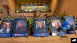 The photos of the killed police officers line the stage during a candle light vigil at City Hall on July 11, 2016, in Dallas.