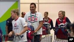 Para anggota delegasi Rusia ke Olimpiade membawa bagasi mereka saat tiba di bandara Rio de Janeiro (29/7). (AP/Leo Correa)