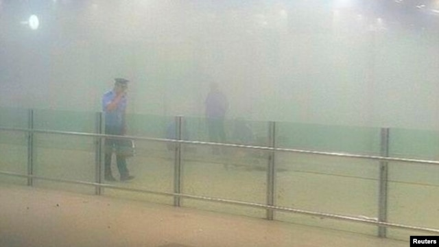 FILE - A policeman stands amid smoke at the arrival gate B after an explosion at Terminal 3 of Beijing Capital International Airport in Beijing, July 20, 2013.
