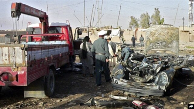 Afghan police inspect the wreckage of a car in which a district chief, his son and a bodyguard were killed by a car bomb in Kandahar, 15 June 2010