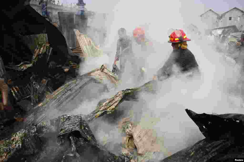 Firefighters attempt to put out a fire in a slum at Modhubagh in Dhaka, Bangladesh. A child was burnt alive and hundreds of shanties were gutted during the fire that originated from a cooking oven in the slum, firefighters said.