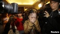 Seorang anggota keluarga penumpang Malaysia Airlines nomor penerbangan MH370 menangis sambil melewati jurnalis di Beijing (9/3).