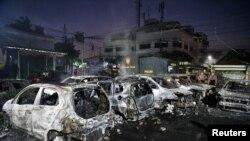 Polisi memeriksa mobil-mobil yang hangus terbakar di Asrama Brigade Mobil (Brimob) di Petamburan, Jakarta, 22 Mei 2019. (Foto: Antara Foto/Sigid Kurniawan via Reuters)