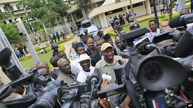 Nigeria's president Goodluck Jonathan (center right) fields questions from journalists as he leaves U.N. headquarters, where a day earlier a suicide bomber crashed through an exit gate and detonated a car full of explosives, in Abuja, Nigeria, August 2011