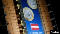 A banner showing a Latvian euro coin is seen on the facade of the European Commission headquarters in Brussels, Dec. 20, 2013.