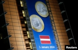 FILE - A banner showing a Latvian Euro coin is seen on the facade of the European Commission headquarters during a European Union leaders summit in Brussels, Dec. 20, 2013.