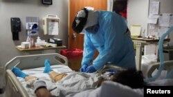 Лікар у Техасі оглядає хвору на COVID-19 пацієнтку